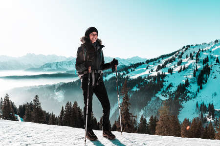 Portrait of young female hiker standing with poles in winter snowy mountains Standard-Bild