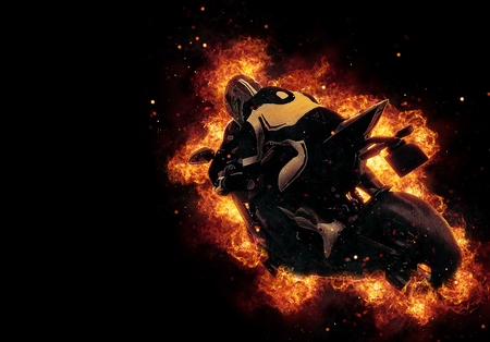 Motorbike rider engulfed in fire and flames as he speeds along on his motorbike with exploding sparks filling the dark background and copy space