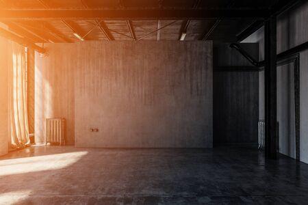 Bright, warm light illuminates an empty, abandoned concrete warehouse room.