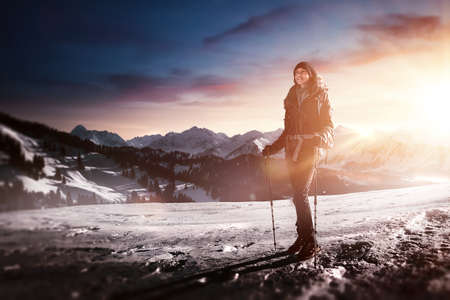 Young woman trekking on a cold winter morning walking across a frozen snowy mountain landscape with her hiking poles and backpack backlit by the glow of the rising sun Stock Photo