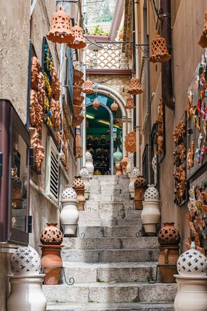 Clay or earthenware containers and decorations on a narrow steep stone staircase in Taormina, Sicily leading to an arched window at the top Banque d'images - 128882092