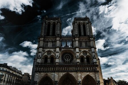 Low angle front view of Notre-Dame Cathedral against cloudy sky, Paris, France