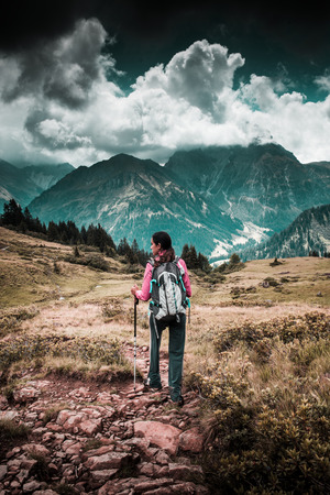 Young woman backpacking or trekking in the mountains walking along a stony path across a grassy plateau towards distant rugged alpine mountain peaks Stock Photo