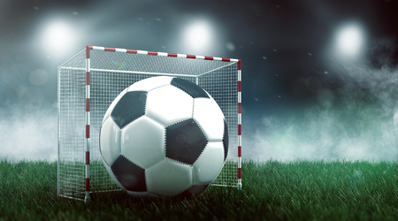 Soccer ball in small goal on green lawn against stadium lights, viewed from low angle. Football championship concept. 3d Rendering