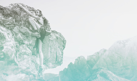 Cold blue toned misty image of a woman with a backpack mountain climbing stretching for handholds over a high altitude rock face in a concept of extreme sport