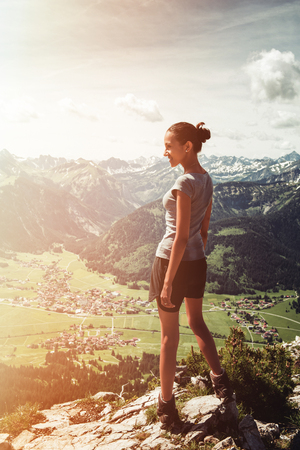 Athletic fit young woman hiker standing on a mountain summit in the glow of the rising sun admiring the green verdant alpine valley below her in a healthy active lifestyle and fitness concept