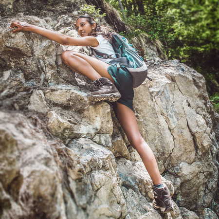 Young woman wearing a backpack free climbing on a steep rocky mountain cliff face in a concept of an active healthy lifestyle ad extreme sports Stock Photo