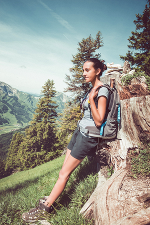 Young fit woman hiker wearing a backpack perching on a felled tree trunk on a steep slope enjoying the beauty of the mountains looking out over rugged peaks and valleys