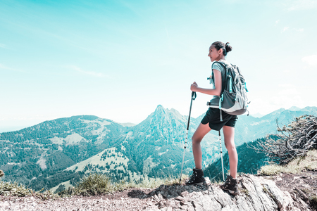 Athletic fit young woman hiking in the mountains standing on a rocky ledge or summit viewing the steep valleys and surrounding alpine peaks with copy space in a health and fitness concept Stock Photo