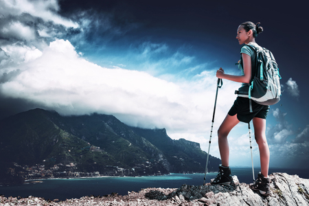 Young woman hiking along a picturesque coastline standing on a rocky ridge with her backpack and poles looking out over the ocean and bay