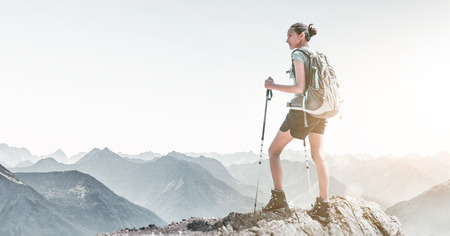 Fit active young woman watching a mountain sunrise as she stands with her backpack and hiking poles on a rocky peak overlooking a panoramic vista of distant rugged ranges in an atmospheric landscape