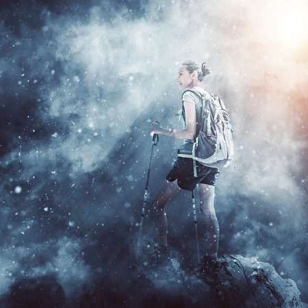 Girl hiking on a summit during snow storm. Epic moody style