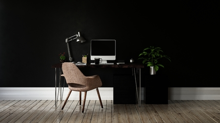 Monitor and desk lamp on black table with metal legs and brown chair on tan wood floor in front of completely black wall