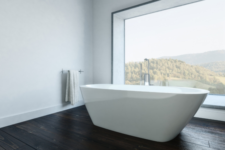 Minimalist white walled bathroom with modern white tub and towel holder. Mountain landscape outside window.