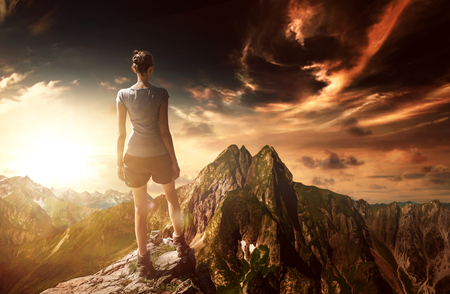 Unidentifiable female mountain climber standing on rocky cliff in front of wide alpine range with dark clouds above Stock Photo