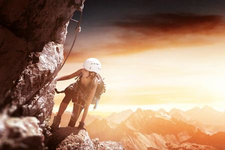 Determined woman wearing safety equipment while climbing a high and dangerous rocky mountain at sunset