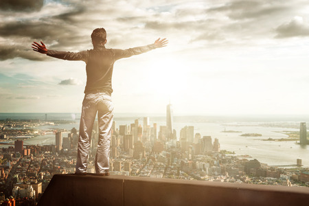 Unidentifiable joyful man with outstretched arms standing on metal beam above cityscape during the day. Includes copy space.