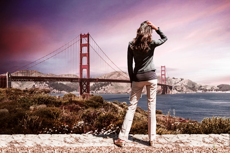 One unidentifiable woman wearing black sweater and tan pants in foreground standing in front of Golden Gate Bridge