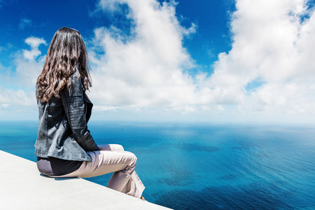 Woman facing away from camera sitting on white platform overlooking clear blue ocean and puffy white clouds in sky during daytime Фото со стока