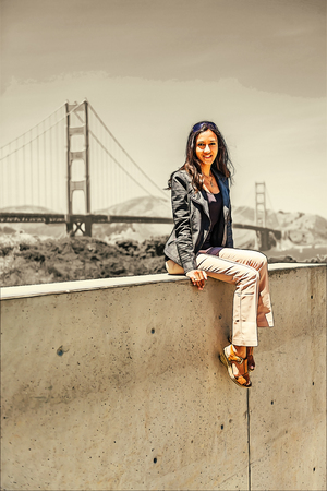 Woman wearing black sweater looking at camera while sitting on concrete wall with suspension bridge in background.