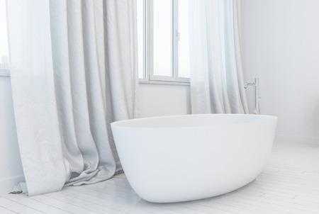 One single glossy white minimalist tub with metal spigot next to window on top of white wooden plank floor Stock Photo