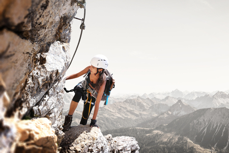 Fit sporty young woman mountain climbing in rugged terrain standing holding a steel cable on a precipitous rocky cliff at high altitude above distant alpine peaks Stock Photo