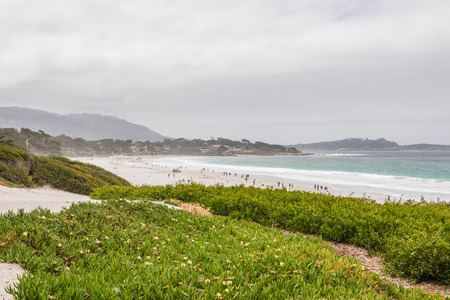 CARMEL-BY-THE-SEA, USA - May 13 2018: People enjoying a day on a tropical beach at Carmel-by-the-Sea, California on an overcast summer day in a scenic view of the Pacific Ocean and coastline Stock Photo