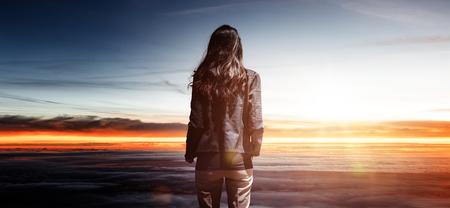 Trendy slender woman watching the sunrise standing above the cloud layer looking out at a tranquil colorful orange sky with sun flare in a conceptual image Stock Photo