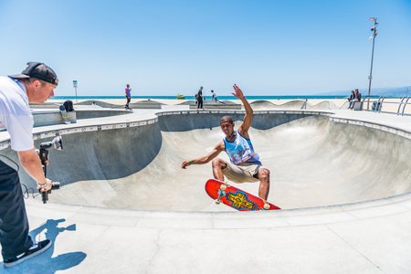 LOS ANGELES, USA - May 15 2018: Man filming an athletic young skateboarder performing for the camera at an outdoor skate park in Venice beach, Santa Monica, Los Angeles, California