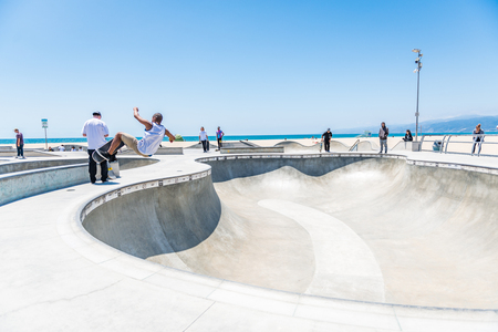 LOS ANGELES, USA - May 15 2018: Young man working out skateboarding at an outdoor beachfront skate park in Venice Beach, Santa Monica, Los Angeles, California on a sunny summer day Editorial