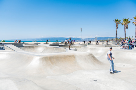 LOS ANGELES, USA - May 15 2018: Young men skateboarding at a skate park at the beachfront in Santa Monica, Los Angeles on a hot sunny summer day Editorial