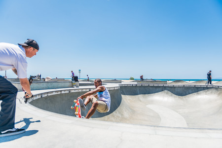 LOS ANGELES, USA - May 15 2018: Photographer filming a young man skateboarding at the open air skate park on the beachfront in Venice Beach, Los Angeles, California Editorial