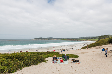 CARMEL-BY-THE-SEA, USA - May 13 2018: People enjoying a day on a tropical beach at Carmel-by-the-Sea, California on an overcast summer day in a scenic view of the Pacific Ocean and coastline Editorial