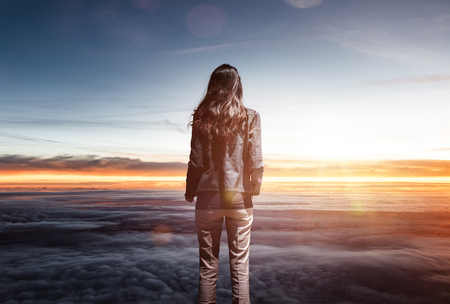 Trendy slender woman watching the sunrise standing above the cloud layer looking out at a tranquil colorful orange sky with sun flare in a conceptual image Editorial