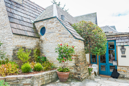 CARMEL-BY-THE-SEA, USA - May 13 2018: Picturesque stone cottage or house in Carmel-by-the-Sea, Monterey Peninsula, California, with neat garden and blue entry door