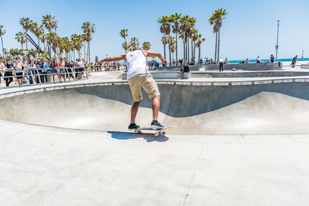LOS ANGELES, USA - May 15 2018: Skilled young man keeping the balance on skateboard on the edge of a bowl in a modern skate park in a sunny day in LA