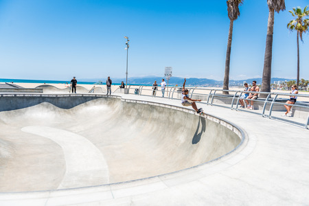 LOS ANGELES, USA - May 15 2018: People watching a young man skateboarding at an outdoor waterfront skate park in Venice beach, Santa Monica, Los Angeles, California