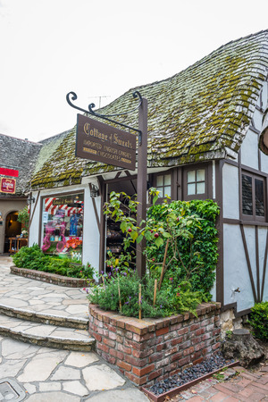 CARMEL-BY-THE-SEA, USA - May 13 2018: Picturesque stone cottage or house in Carmel-by-the-Sea, Monterey Peninsula, California, with neat garden and wooden door