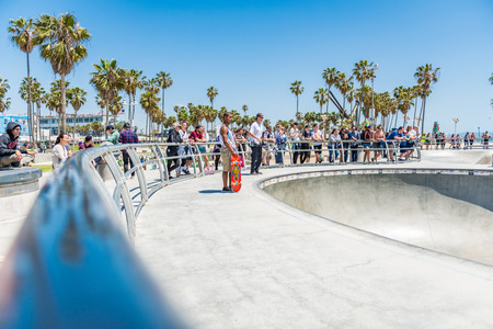 LOS ANGELES, USA - May 15 2018: Group of people watching skateboarders at a beachfront skating park in Los Angeles, California with tropical palm trees behind