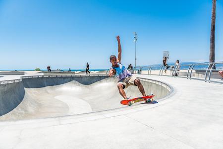 LOS ANGELES, USA - May 15 2018: Young man practicing his skateboarding skills at the beachfront skate park in Santa Monica, Los Angeles, California