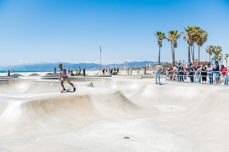 LOS ANGELES, USA - May 15 2018: People watching young men skateboarding at an outdoor rink in Venice Beach, Santa Monica, Los Angeles, California on a hot summer day