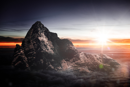 Fiery sunset over a rugged alpine mountain peak with a sunburst in the colorful orange sky illuminating the steep rocky cliffs and sun flare