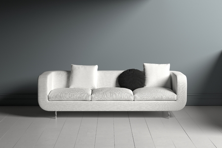 Lone white couch with square and circular black pillows sitting in dimly lit room with white wooden floor panels Banque d'images - 125593933
