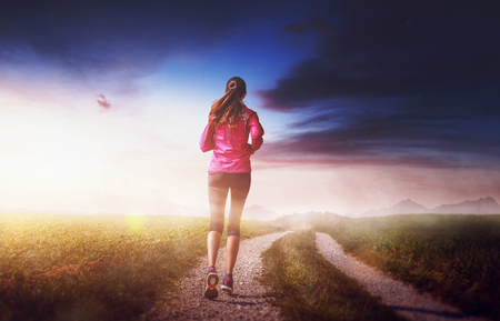 Slim fit woman jogging on a dirt track through grassland at sunrise with a bright glow on the horizon over distant mountains viewed from the rear in a health and fitness concept Banque d'images - 127050489