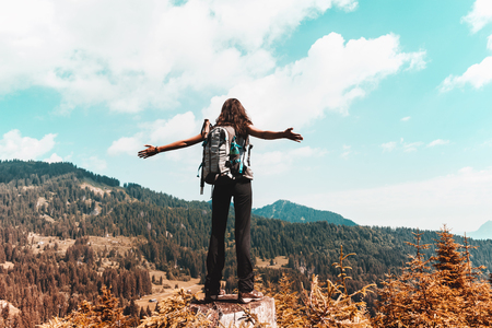 Young woman with backpack spreading her arms while enjoying nature in mountains