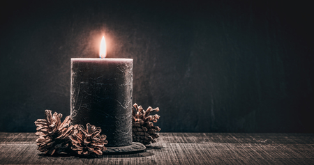 burning candle on a black background.
