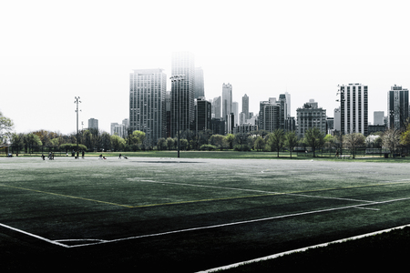 View of Chicago skyline over a deserted sportsground on a bleak grey day with the skyscrapers of the CBD under a high key sky 版權商用圖片