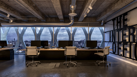 Modern internet company office interior with panoramic view of the city. Desk with several workplaces and ventilation system pipes on concrete ceiling