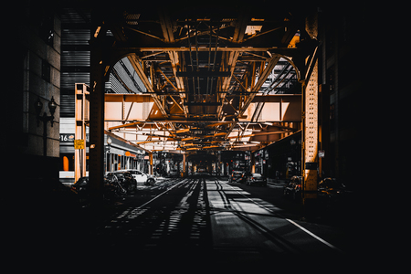 Night scene in Chicago, USA with a view under receding steel girders to a car in the street in front of commercial buildings 版權商用圖片
