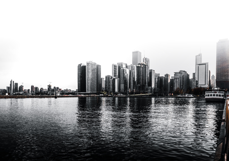 City skyline with reflections of the CBD skyscrapers on the water in Chicago, USA in a black and white urban landscape